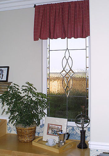 A curved centerpiece in the window adds an eclectic appeal to any room that is based on lines. This window uses curved lead lines to great effec